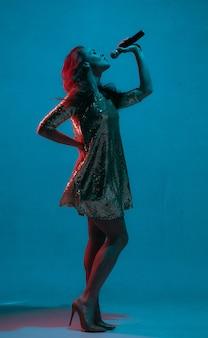 네온 불빛에 파란색 스튜디오 배경에 고립 된 백인 여성 가수 초상화. 마이크와 밝은 드레스에서 아름 다운 여성 모델입니다. 인간의 감정, 표정, 광고, 음악, 예술의 개념.