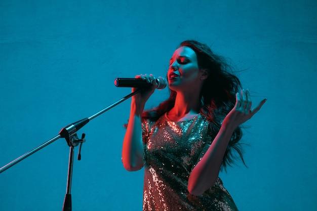 Портрет кавказской певицы, изолированные на синем фоне студии в неоновом свете. красивая женская модель в ярком платье с микрофоном. понятие человеческих эмоций, выражение лица, реклама, музыка, искусство.