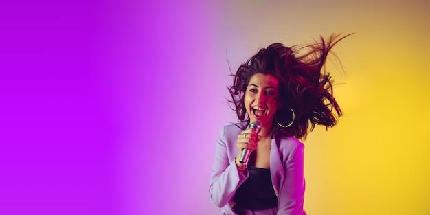 Портрет кавказской певицы изолирован на градиентном студийном фоне в неоновом свете, флаер с copyspace для рекламы