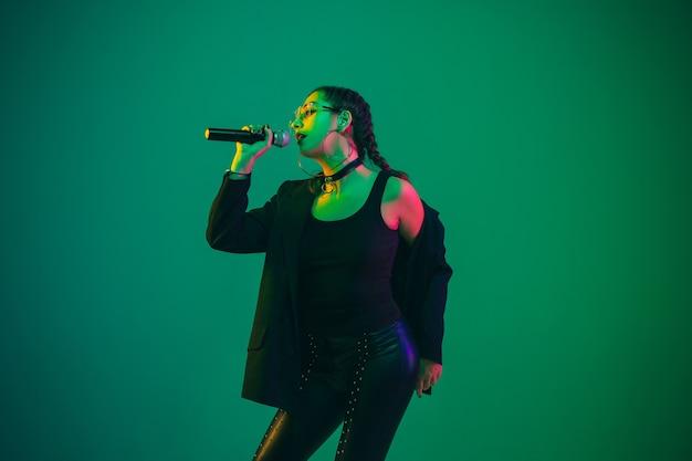 Портрет кавказской певицы, изолированной на зеленой студии в неоновом свете