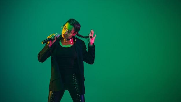 ネオンの光の緑の壁に分離された白人女性歌手の肖像画。マイク付きの黒い服を着た美しい女性モデル。人間の感情、顔の表情、広告、音楽、アートの概念。