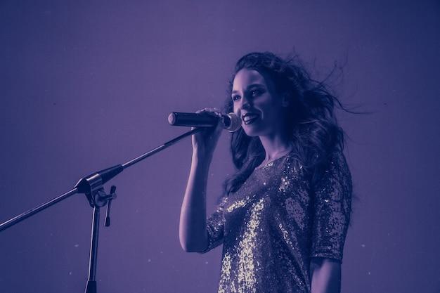 Ritratto di cantante femminile caucasico isolato su studio viola in luce al neon