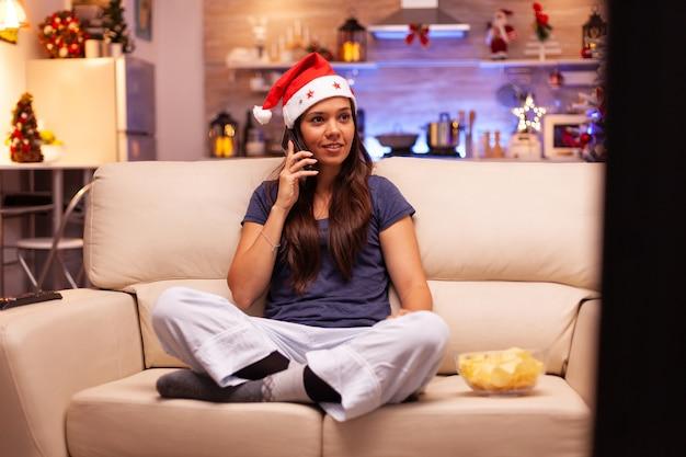Кавказская женщина сидит в позе лотоса, разговаривает с другом на смартфоне