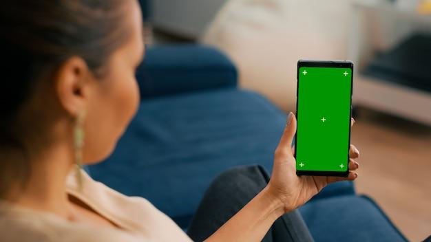거실 소파에 앉아 있는 백인 여성은 녹색 화면 크로마 키 디스플레이가 있는 전화를 사용하여 인터넷 앱에서 사교 활동을 하고 있습니다.