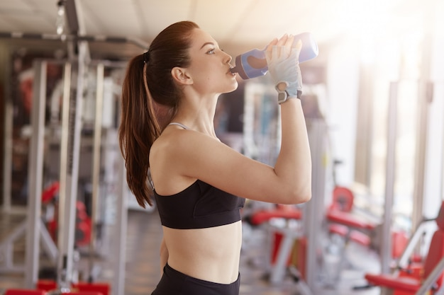 Caucasian female in sportswear drinking water after exercising, lady with ponytail having rest between sets.