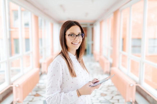Caucasian female teacher with eyeglasses using tablet and looking at camera while standing in the hall
