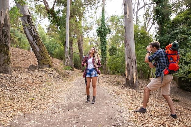 森の中の道路で写真のポーズをとって、バックパックを運ぶ白人女性旅行者。カメラを持って彼女を撃っている若い男。自然の上で一緒にトレッキングするカップル。観光と休暇の概念