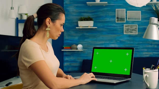Caucasian female typing on laptop computer with mock up green screen chroma key display for online communication sitting on desk table