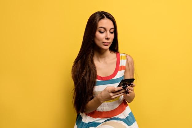 Caucasian female university student wearing brightful dress looking at smartphone smiling happy