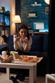 Кавказская женщина смотрит развлекательный фильм по телевизору во время доставки еды на вынос