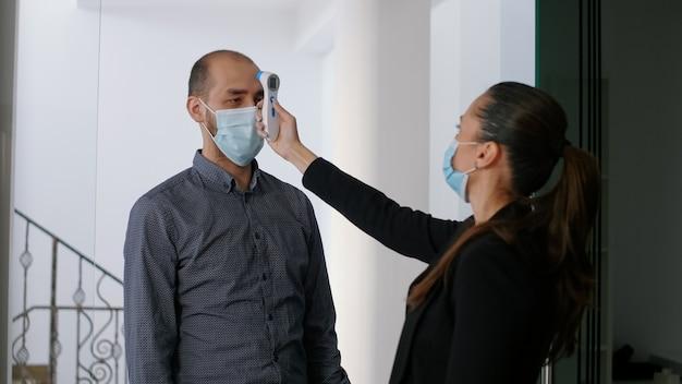적외선 온도계를 사용하여 작업자의 체온을 확인하는 얼굴 마스크를 쓴 백인 여성. 바이러스 질병 감염을 피하기 위해 새로운 정상 회사 사무실에서 사회적 거리를 존중하는 팀
