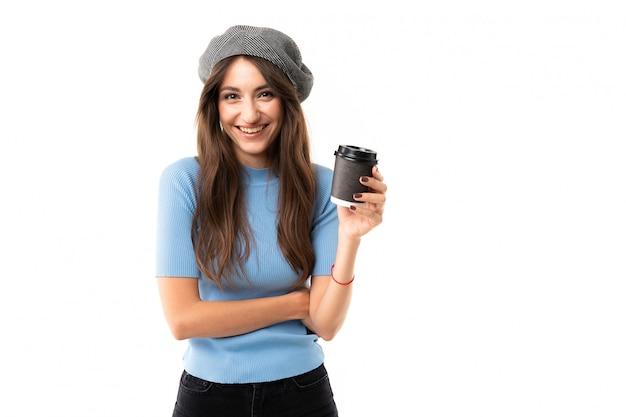 キャップを持つ白人女性は、コーヒーと笑顔、分離された画像を飲む