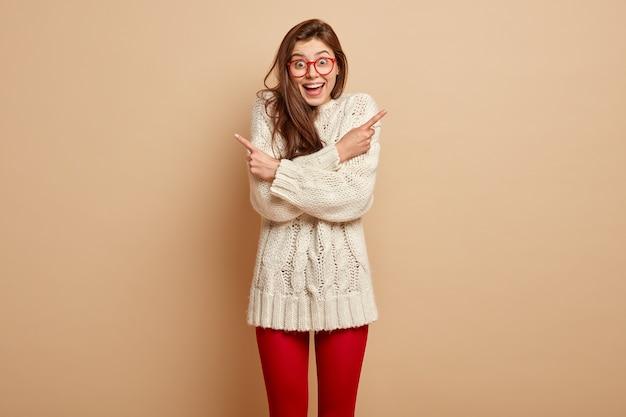 Femmina caucasica con espressione felice, tiene le mani incrociate, ha dubbi, sorride ampiamente, punta su lati diversi con spazio vuoto per la pubblicità, indossa un maglione lavorato a maglia, isolato su un muro beige