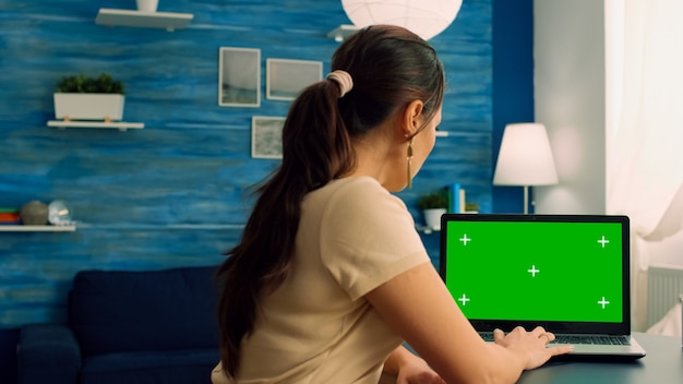 Caucasian female working on laptop computer with mock up green screen chroma key display for personal business
