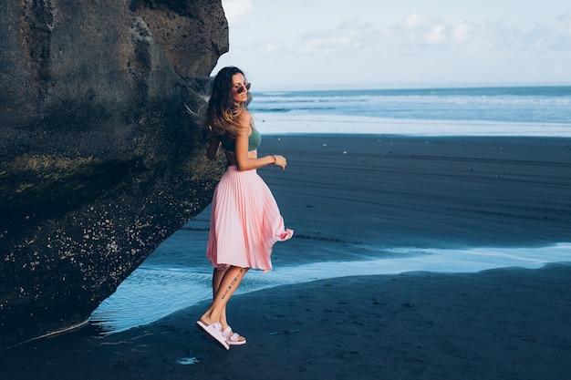 Donna abbronzata in forma caucasica in minuscolo top e gonna rosa sulla spiaggia di sabbia nera