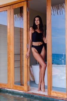 Caucasian fit tanned woman wearing vintage old bikini, posing at luxury hotel villa