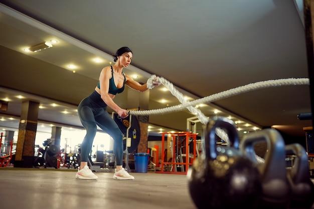 ジムでバトルロープでトレーニングをしているsportsoutfitに身を包んだ白人フィットの女性