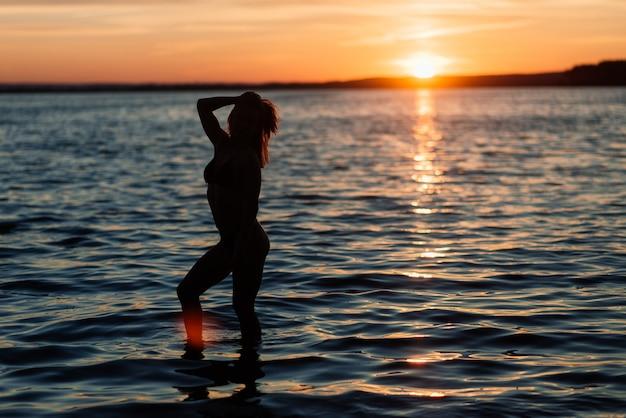 スポーツボディを持つ白人のフィット女性は日没時にビーチでポーズします。夏、やる気による減量。