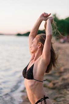 スポーツボディを持つ白人のフィットの女性は、日没時にビーチでポーズをとっています。夏までに減量。