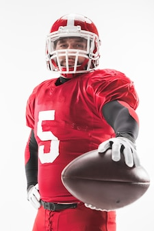 Caucasian fitness man as american football player holding a ball on white background