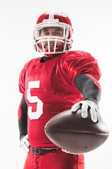 Uomo caucasico di forma fisica come giocatore di football americano che tiene una palla su priorità bassa bianca