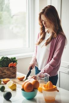 赤い髪とそばかすが果物をカットし、オレンジとレモンからキッチンで天然フレッシュジュースを作る白人フィットネスの母親