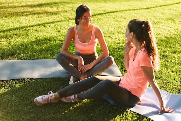 녹색 공원에서 잔디에 앉아있는 동안 웃고 함께 이야기하는 스포츠웨어의 백인 피트 니스 여성