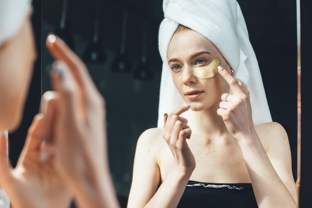 Caucasian freckled woman is applying golden hydrogel eye patches under eyes after taking a shower and cover her head with a towel