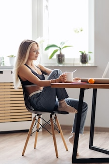 La donna caucasica freelance lavora da casa. la femmina tiene il tè che chiacchiera o che guarda il film usa il laptop.