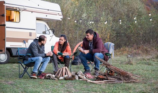 レトロなキャンピングカーで山で一緒にキャンプする白人の友達。キャンプファイヤーを設定します。