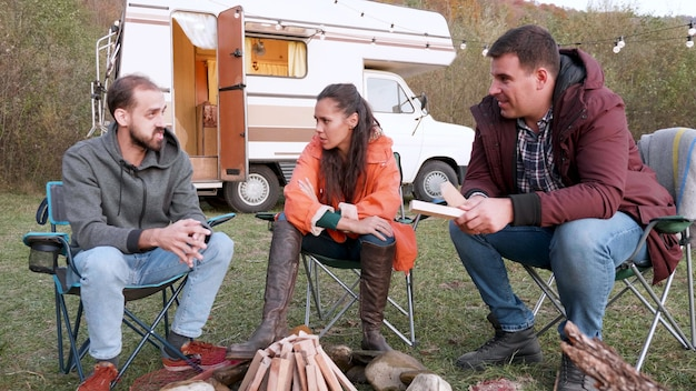 Caucasian friends relaxing together in front of their camper van. camping tent. wood for camping fire.