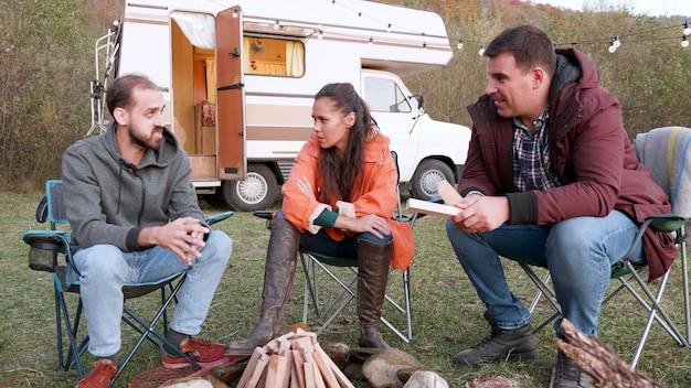 백인 친구들이 캠핑카 앞에서 함께 휴식을 취하고 있습니다. 캠핑 텐트. 캠핑 파이어 용 목재.