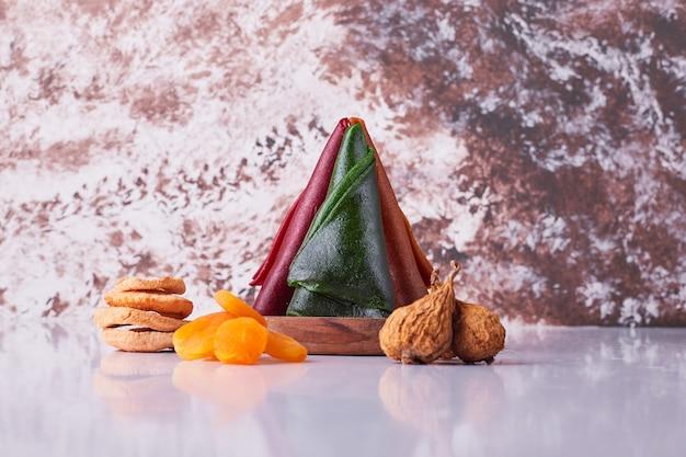 白い背景の上のドライフルーツと木製の大皿に白人のフルーツラヴァッシュ。高品質の写真