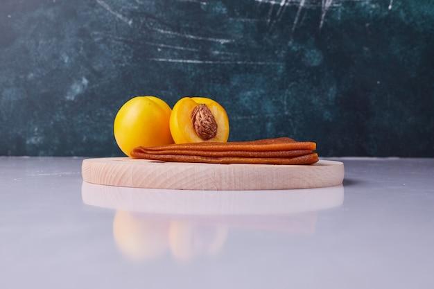 青の背景に白のプレートに黄色の桃と白人のフルーツラヴァッシュ。高品質の写真