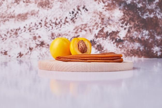 Кавказский фруктовый лаваш с желтыми персиками в белой тарелке на мраморе.
