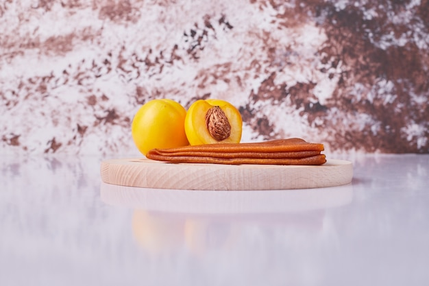 Caucasian fruit lavash with yellow peaches in a white plate on marble.