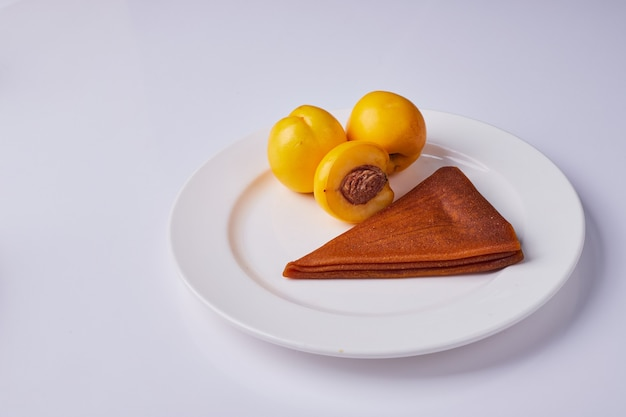 Caucasian fruit lavash with yellow peaches in a white plate.