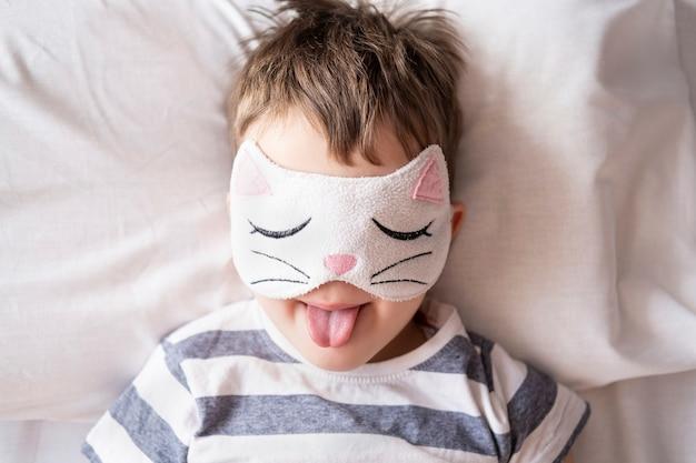 Caucasian funny preschool boy in kitty eye mask striped pyjamas lying in white bed.