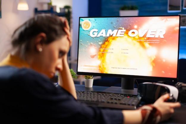 白人ゲーマーは、プロの強力なコンピューターでスペースシューティングゲームの競争に負けています。最新の機器を使用して新しいグラフィックスでオンラインゲームをストリーミングするプロゲーマー