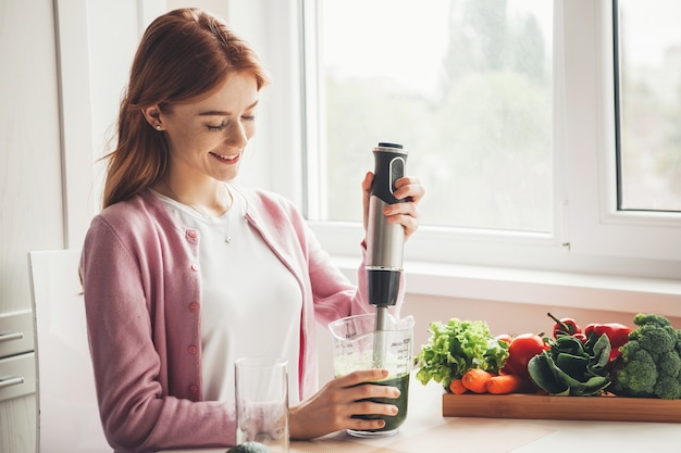 백인 생강 주근깨가 있는 여성이 부엌에서 웃고 있는 압착기로 야채 주스를 짜내고 있다