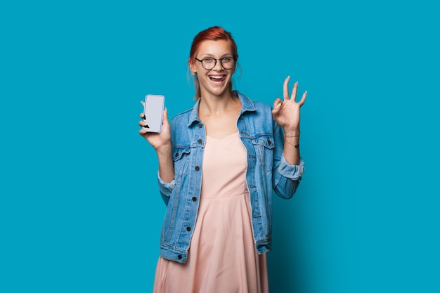 Caucasian ginger woman is gesturing the okay sign while showing the phone screen with empty space  posing on blue  wall