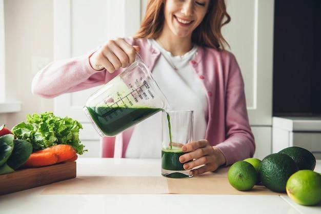 Кавказская рыжая женщина наливает свежий зеленый сок в стакан после отжима из лайма и авокадо