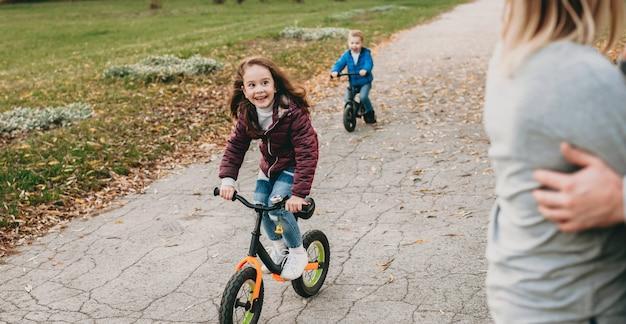 抱きしめる両親を見ながら公園で自転車に乗る白人の女の子と彼女の兄弟