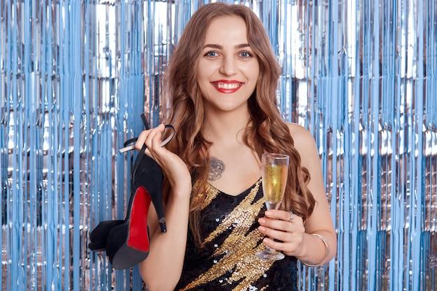 새해 파티에 백인 소녀, 곱슬 여자는 생일을 축하하고 샴페인을 마시고, 은색 반짝이 반짝이에 대해 손에 신발과 함께 포즈를 취하는 세련된 드레스를 입는다.