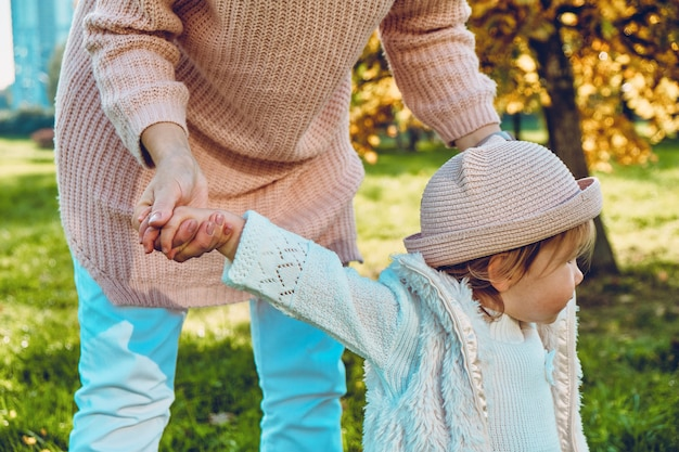 Кавказская девочка учится ходить с мамой в парке.
