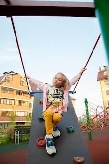 白人の女の子が遊び場のクライミングウォールを登る