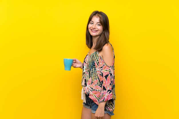 Caucasian girl in colorful dress holding hot cup of coffee