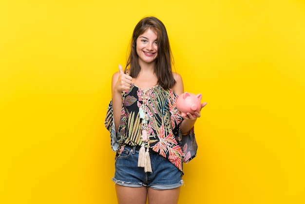Caucasian girl in colorful dress over isolated yellow background holding a big piggybank