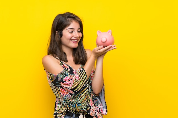 Caucasian girl in colorful dress over isolated yellow wall holding a big piggybank
