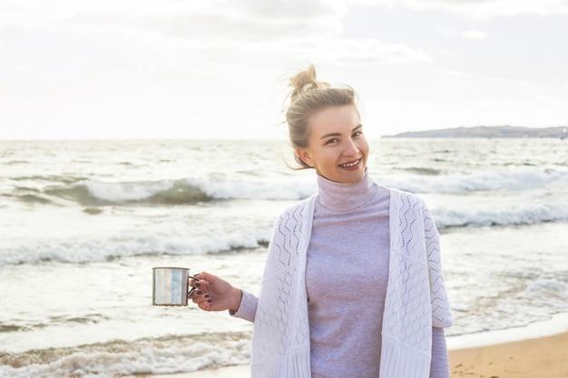 Кавказская девушка любит природу и путешествовать к морю в ветреный осенний день.